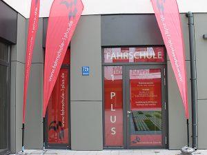 Fahrschule 1plus, Eingang mit Beachflags, München Neuperlach